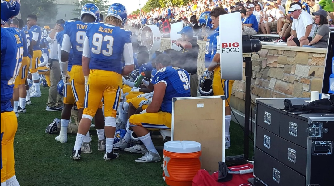 Big Fogg Misting Fans cooling down the football team with blue jersey in crowded stadium