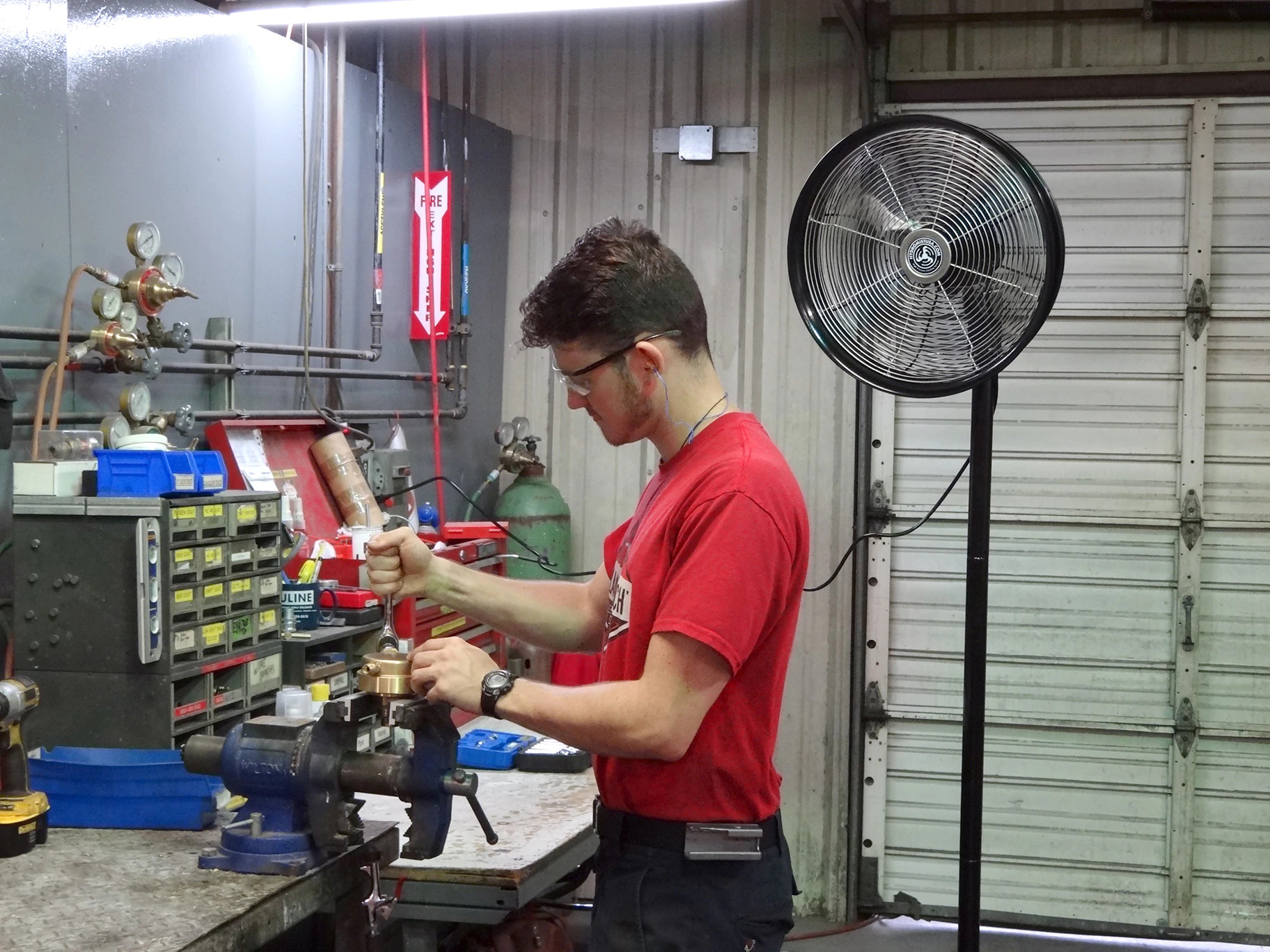 Worker wearing red t-shirt and black work pants working in his workshoup under 18 Inch Shrouded Ocscillating Outdoor Indoor Fan-3 Speeds