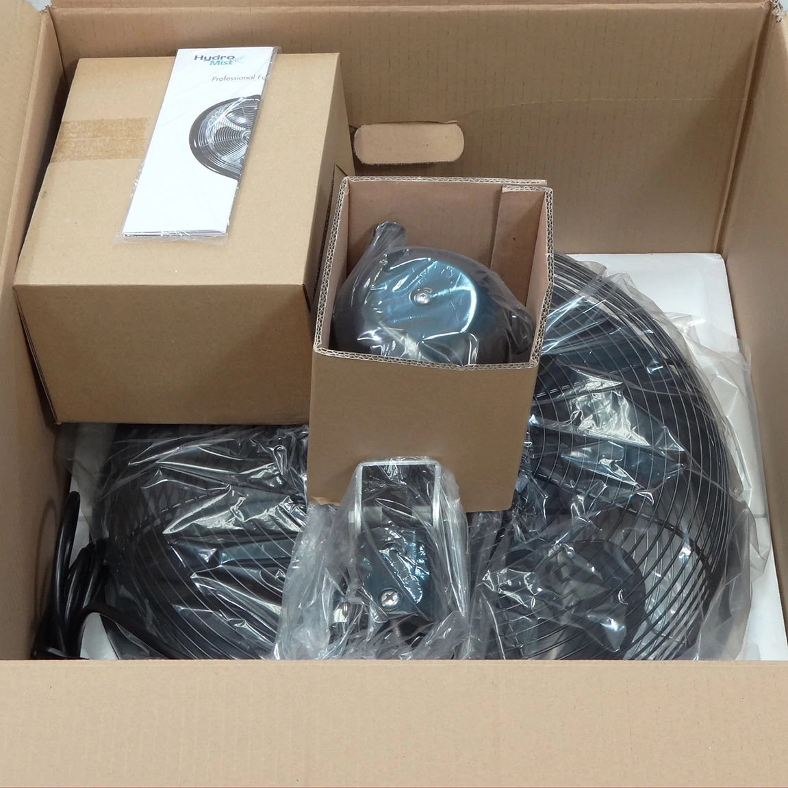 Open packaged box containing 24 Inch Shrouded Ocscillating Outdoor Indoor Fan