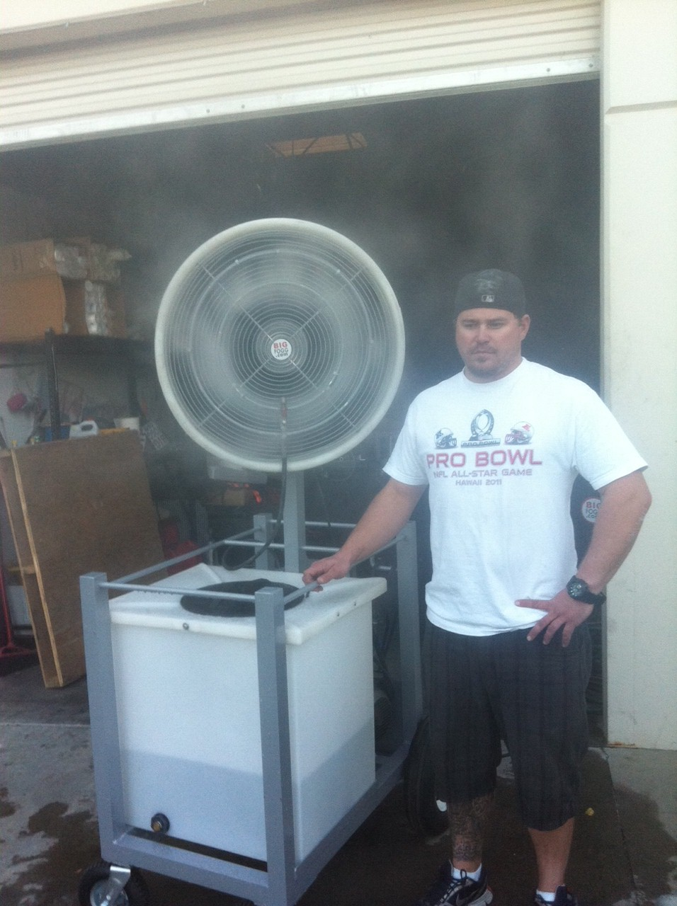 Man wearing black hat,pants and white pro bowl shirt standing beside Big Fogg High-Pressure Misting Fan with 40' Gallon Tank