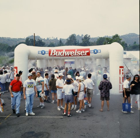 People standing under High Pressure 20' X 20' misting inflatable in a budweiser sponsored mathon.